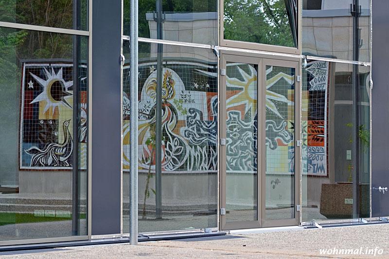 """Auch die Terrassen- und Gartenanlagen auf der dem Schlosspark zugewandten Seite des Hauses beeindrucken. Hier spiegelt sich das restaurierte Womacka-Mosaik """"Erde, Wasser, Feuer, Luft"""" in den gigantischen Panoramafenstern der Erdgeschoss-Suiten."""