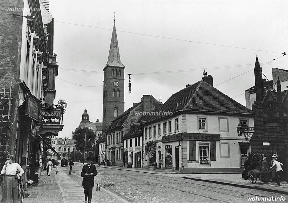 Die Schlossstraße in der Köpenicker Altstadt um 1910. Am rechten Bildrand der Eingang zum Rathaus an der Ecke Rosenstraße. Dahinter Bürgerhäuser aus dem 18. Jahrhundert, von denen das Andersonsche Palais (3. Gebäude von rechts) mit seinen barocken Formen besonders herausragt. Hinter dem Turm der Laurentiuskirche ist das Kuppeltürmchen auf dem Dach des Bankhauses Köpenick an der Ecke Schlossstraße / Freiheit gut zu erkennen.