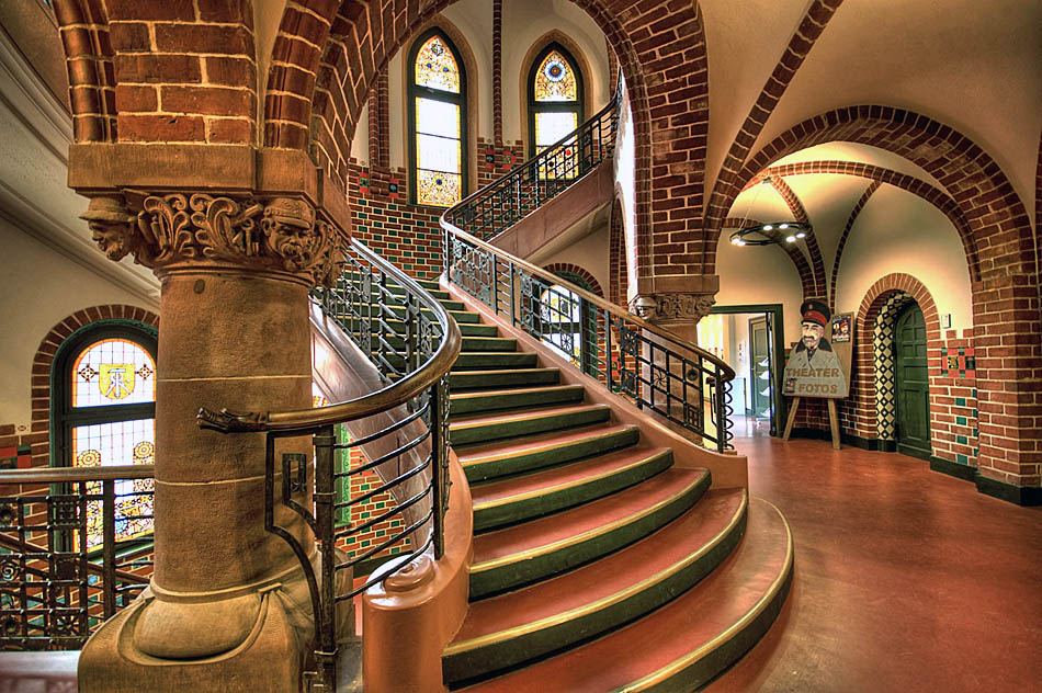 Bunte Glasfenster tauchen das ohnehin schon farbenprächtige Treppenhaus des Rathauses Köpenick in ein weiches Licht. Foto: Sebastian Niedlich, (Grabthar bei flickr,com), Veröffentlicht unter Creative-Commons-Lizenz.