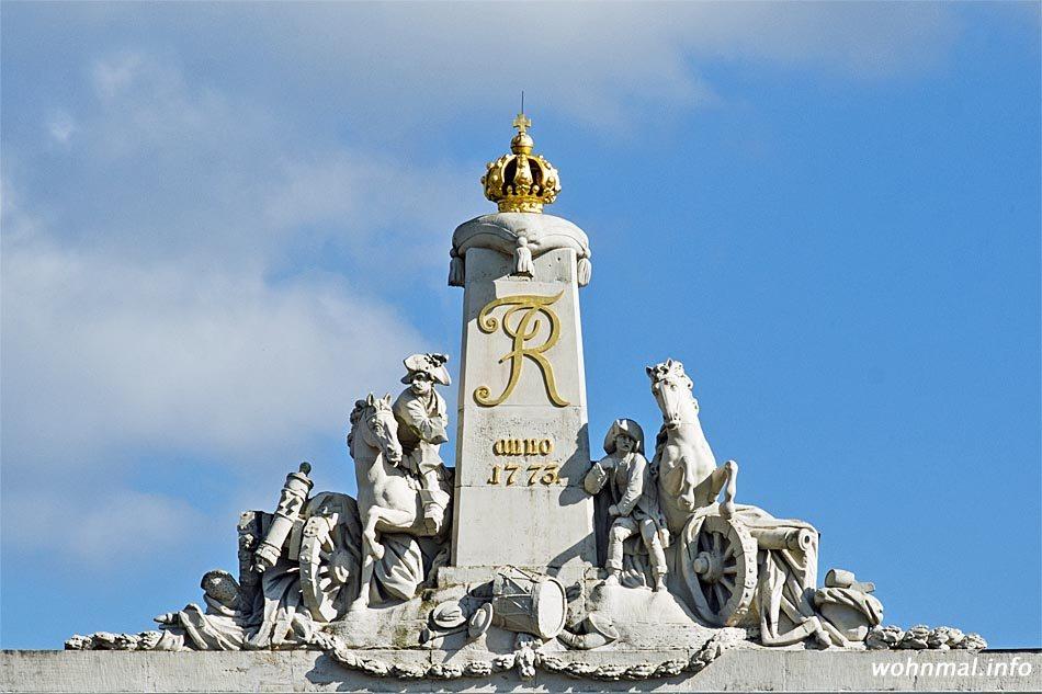 """Die aus Ummendorfer Sandstein gefertigte Boumann-Skulptur steht auf einer barocktypischen Atiika. Sie zeigt einen berittenen Tambourmajor (der ursprünglich vorhandene Tambourstab fehlt) und einen Artilleristen, zwei Pferde und zwei Kanonen in dramatischer Aktion. In der Mitte ragt ein gekrönter Obelisk mit vergoldetem Monogramm Friedrichs des II. (FR = Fredericus Rex) sowie die Anschrift """"anno 1773"""". Sie verweist auf das Gründungsjahr des """"Potsdamer Artillierie-Commandos"""". Aus dieser Einheit ging später das 2. Garde-Feldartillerie-Regiment hervor. Foto: Sven Hoch"""